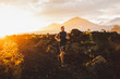 Young male athlete trail running in mountains at sunrise. Amazing black lava volcanic landscape of Bali on background. Adventure sport concept.