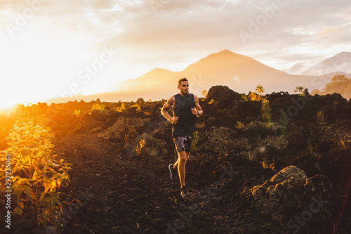 Young male athlete trail running in mountains at sunrise Fototapete