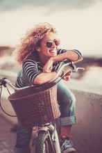 Cheerful Trendy Young Adult Caucasian Woman Sitting On A Bike And Smiling - Beautiful Female Portrait - Concept Of Outdoor Leisure Activity And Happiness And Joyful Lifestyle