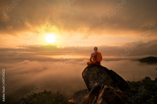 Buddhist monk in meditation at beautiful sunset or sunrise background on high mountain