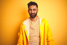 Young Indian Man Wearing Raincoat Standing Over Isolated Yellow Background Winking Looking At The Camera With Sexy Expression, Cheerful And Happy Face.