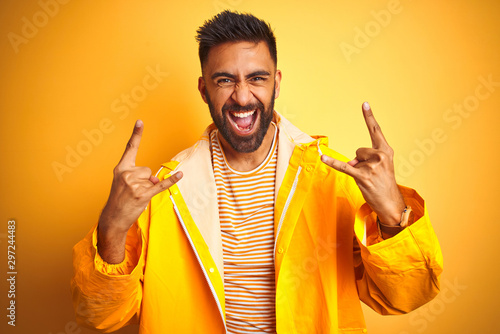 Young indian man wearing raincoat standing over isolated yellow background shouting with crazy expression doing rock symbol with hands up Canvas-taulu
