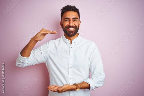 Fototapeta Young indian businessman wearing elegant shirt standing over isolated pink background gesturing with hands showing big and large size sign, measure symbol. Smiling looking at the camera obraz
