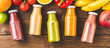 Multicoloured juices in bottles on old wooden background with fruits and vegetables. Top view. Banner
