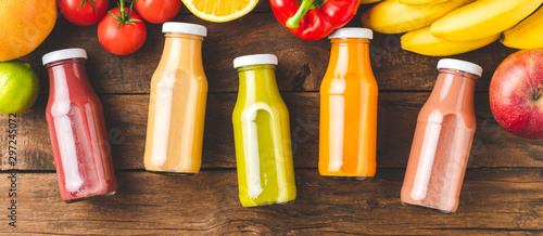 Foto auf Gartenposter Saft Multicoloured juices in bottles on old wooden background with fruits and vegetables. Top view. Banner