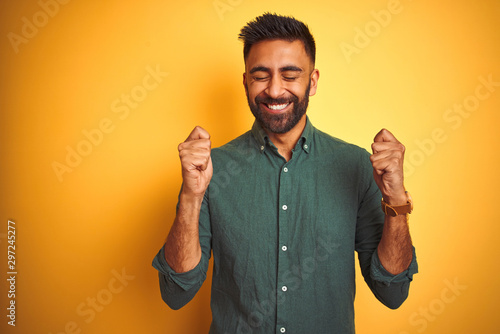 Fotomural  Young indian businessman wearing elegant shirt standing over isolated white background excited for success with arms raised and eyes closed celebrating victory smiling