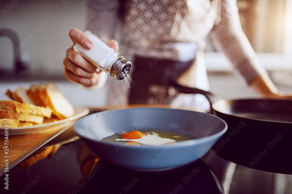 Fototapety, obrazy: Close up of caucasian woman adding salt in sunny side up eggs while standing in kitchen next to stove.