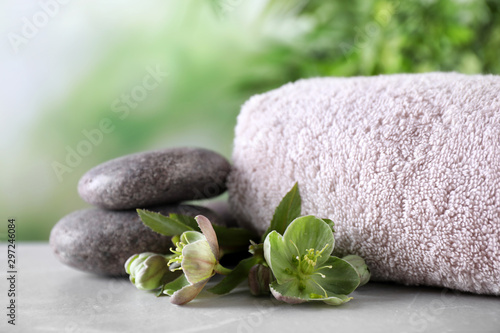 Fotografia  Composition with flowers, spa stones and towel on grey table against blurred bac