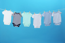 Colorful Baby Onesies Hanging On Clothes Line Against Blue Background. Laundry Day