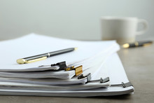 Stack Of Documents With Binder Clips On Light Table, Closeup