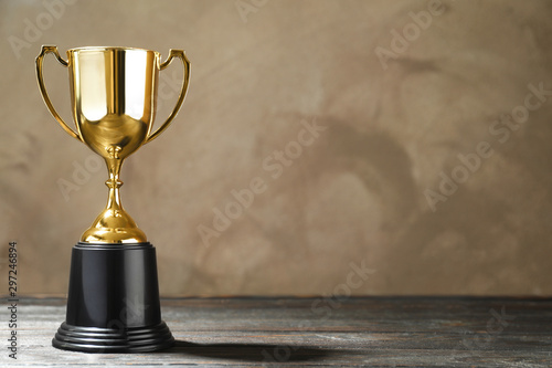 Canvastavla  Golden trophy cup on wooden table against light brown background