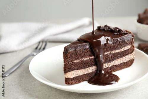 Fototapeta Pouring chocolate sauce onto delicious fresh cake on light table, closeup