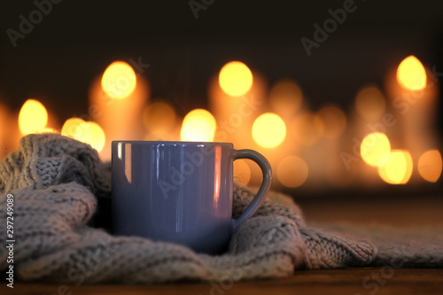 Canvastavla  Cup of hot drink and knitted cloth against blurred background