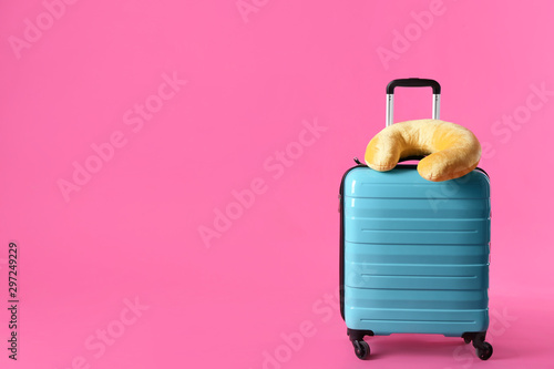 Turquoise suitcase and travel pillow on pink background, space for text Fototapet