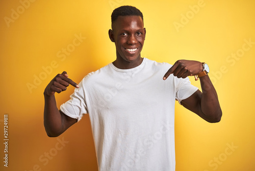 Young african american man wearing white t-shirt standing over isolated yellow background looking confident with smile on face, pointing oneself with fingers proud and happy Poster Mural XXL