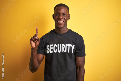 Fototapeta African american safeguard man wearing security uniform over isolated yellow background showing and pointing up with finger number one while smiling confident and happy. obraz na płótnie