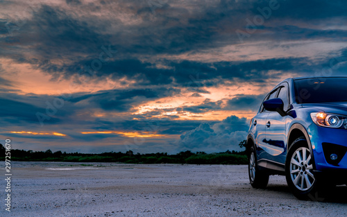 Pinturas sobre lienzo  Luxury blue SUV car parked on land beside tropical forest with beautiful sunrise sky