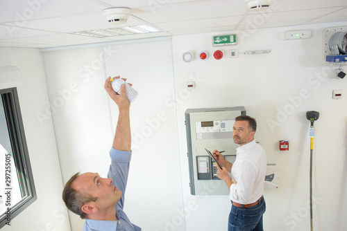 men testing safety detectors on ceiling Canvas-taulu