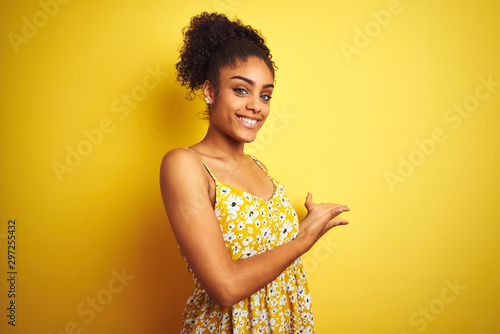 Photo  African american woman wearing casual floral dress standing over isolated yellow