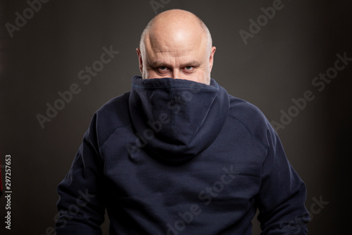Photo Smiling bald man in a hoodie. Humor. Black background.