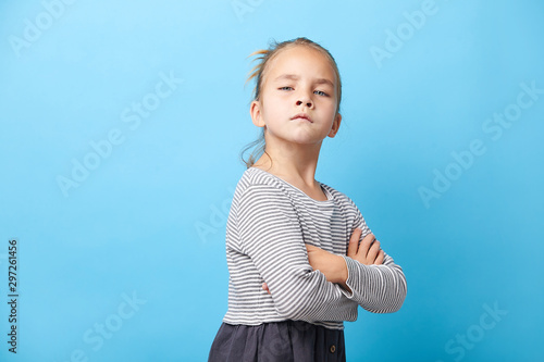Valokuva  Offended little girl crosses her arms and makes a disgruntled expression of protest
