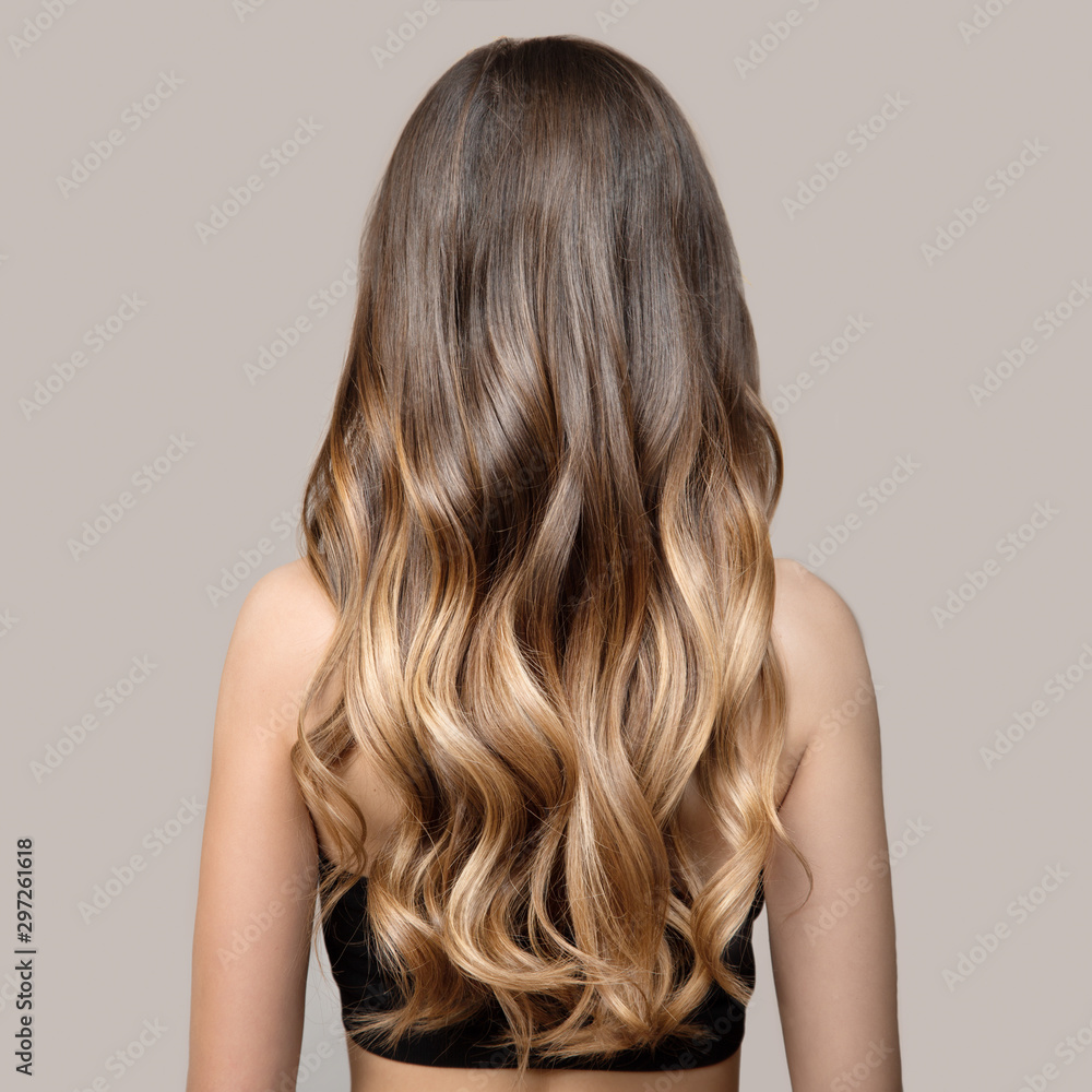 Fototapeta Portrait of a beautiful young brunette woman with long wavy hair. Back view.