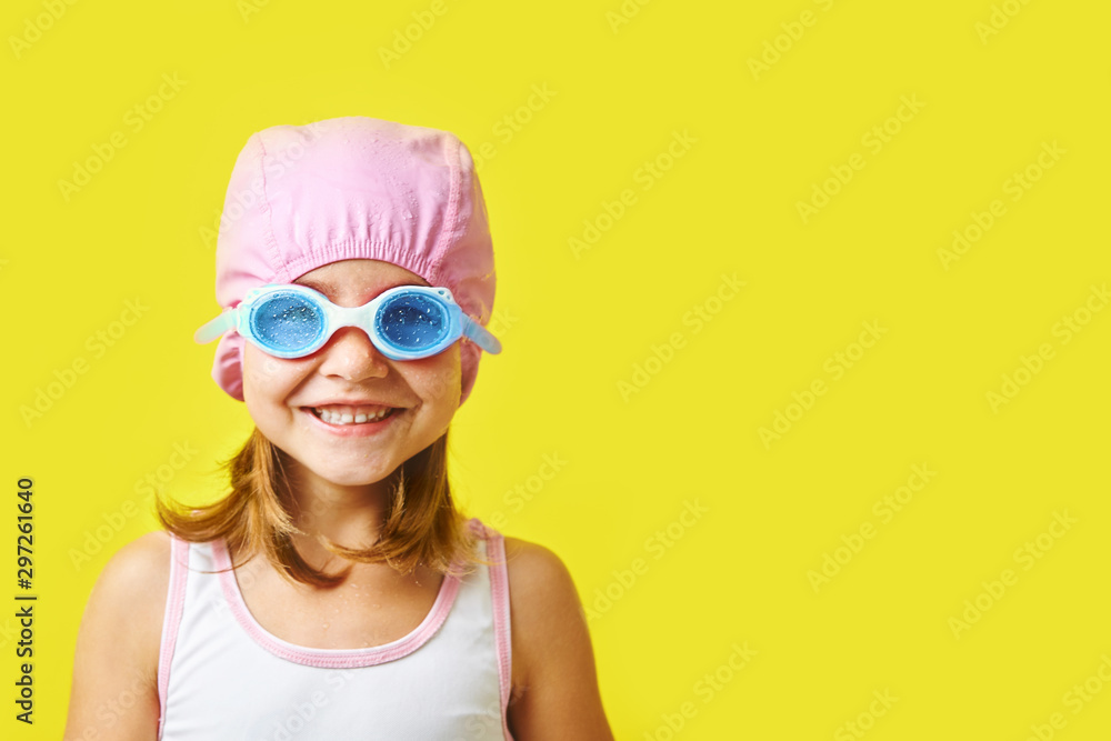 Fototapety, obrazy: Smiling little girl in swimming cap and glasses on colored background with free copyspace.