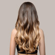 canvas print picture - Portrait of a beautiful young brunette woman with long wavy hair. Back view.