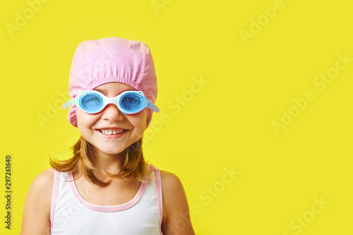 Obraz Smiling little girl in swimming cap and glasses on colored background with free copyspace. - fototapety do salonu