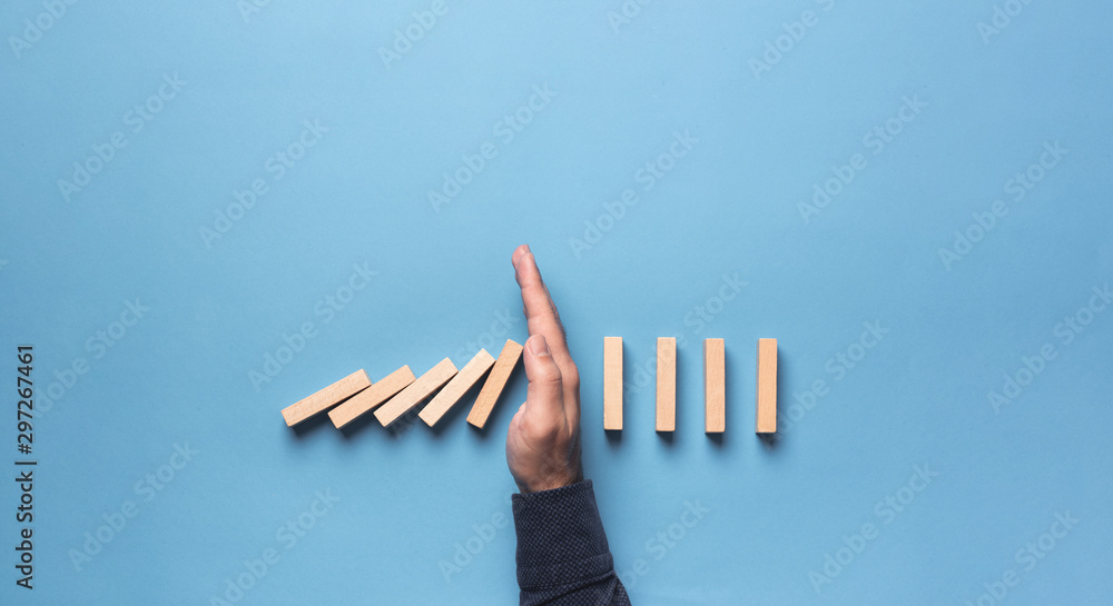 Fototapeta Chain Reaction In Business Concept, Businessman Intervening Chain Dominoes Toppling