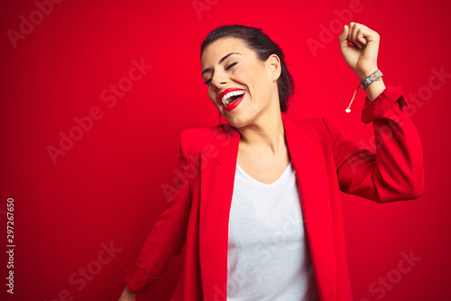 Fotomural Young beautiful business woman standing over red isolated background Dancing hap