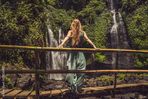 Woman in turquoise dress at the Sekumpul waterfalls in jungles on Bali island, Indonesia. Bali Travel Concept