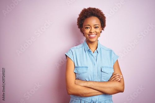 Young beautiful african american woman with afro hair over isolated pink background happy face smiling with crossed arms looking at the camera. Positive person.