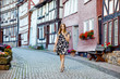 Beautiful young woman with long hairs in summer dress going for a walk in German city. Happy girl enjoying walking in cute small fachwerk town with old houses in Germany.
