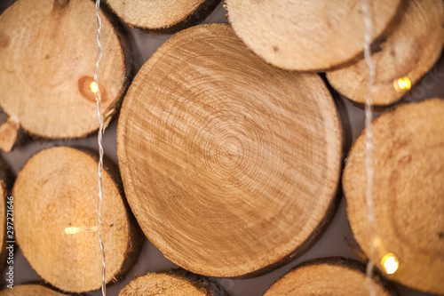 Garden Poster Firewood texture Background of natural wooden saw cuts and christmas garland. Christmas background made of wood and lights for text close-up and copy space.