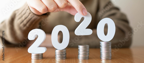 Fototapeta 2020 New year saving money and financial planning concept. Female hands putting white number 2020 on stack of coins. Creative idea for business growth, tax payment, investment and banking. obraz