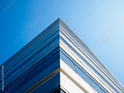 Fototapeta Architecture detail Modern Building Glass facade Corner Blue sky Background obraz