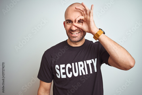 Fototapeta Young safeguard man wearing security uniform over isolated background doing ok gesture with hand smiling, eye looking through fingers with happy face. obraz na płótnie