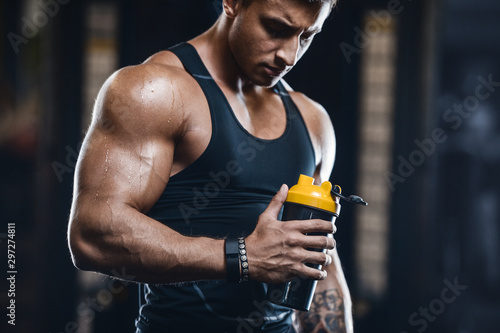 La pose en embrasure Fitness Sport muscular fitness man drinking water after workout cross fitness and bodybuilding concept gym background abs muscle exercises in gym naked torso fitness concept ..