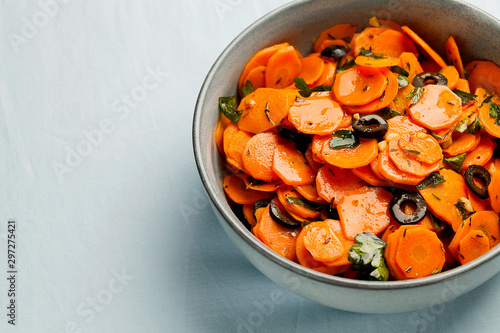 Fototapeta Traditional Moroccan cooked carrot salad North African vegan dish with chopped parsley and olives on gray plate close-up copy space.Healthy organic food for holiday dinner.Horizontal orientation obraz