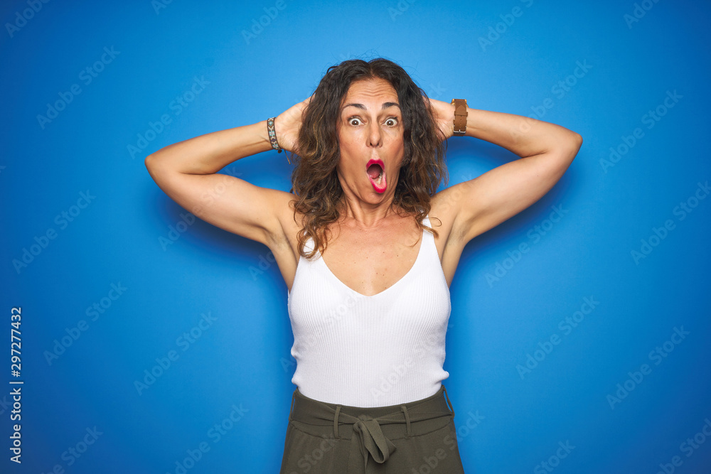 Fototapety, obrazy: Middle age senior woman with curly hair standing over blue isolated background Crazy and scared with hands on head, afraid and surprised of shock with open mouth