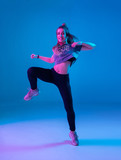 Young stylish girl dancing zumba in the Studio on a colored neon background. Dance poster design.