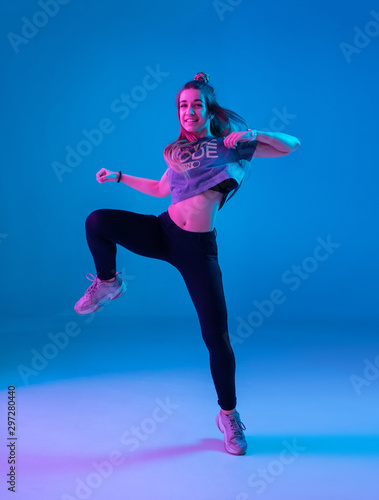Photo Young stylish girl dancing zumba in the Studio on a colored neon background
