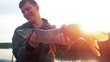 Young amateur angler holds the Pike fish (Esox lucius) in his hands being on the lake with sun on the background