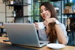 Asian woman working and drink coffee in cafe with laptop computer smile and happy work
