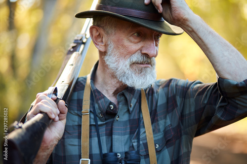 Senior hunter on birds holding gun on shoulder, straighten hat, looking away Canvas-taulu
