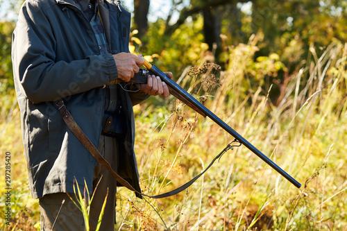 Poster Hunting Hunter man load rifle, shotgun going to shoot on wild animals. Hunting as hobby