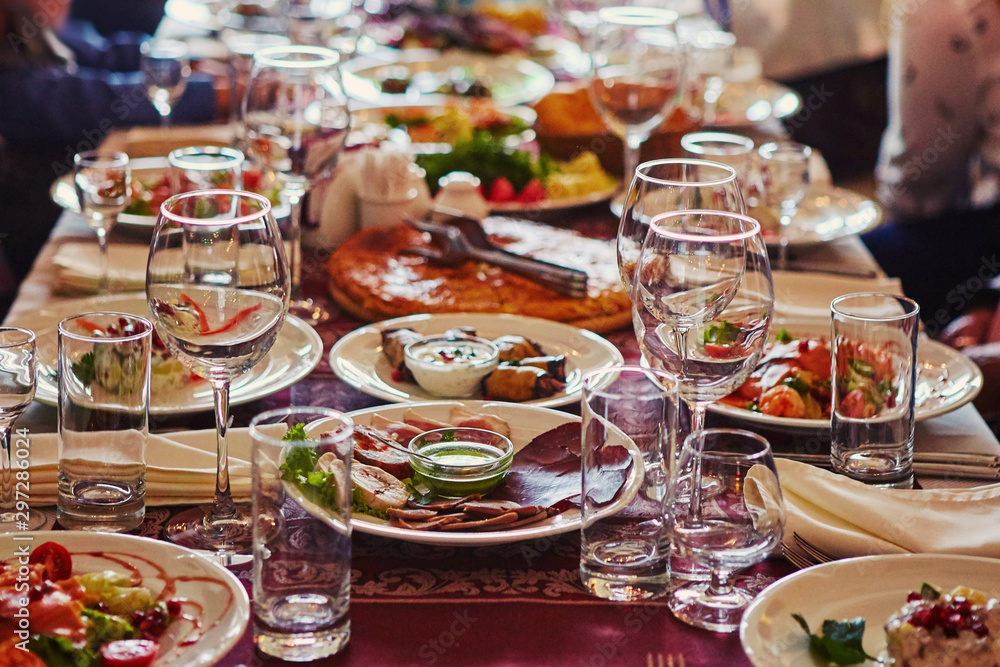 Fototapety, obrazy: A group of people at a long table with food. The concept for the joint celebration of memorable dates or holidays