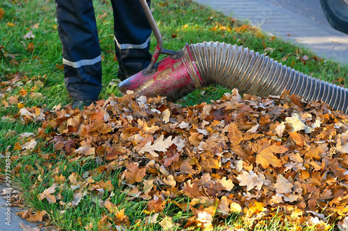 Photo Worker clearing up the leaves using a leaf blower tool..