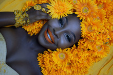 Portrait Of Beautiful African Woman Smiling With Yellow Flowers Around Her Hair And Gold Jewelry On Background